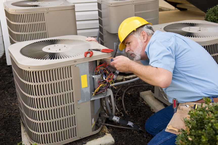 Repairman works on Air Conditioning Unit