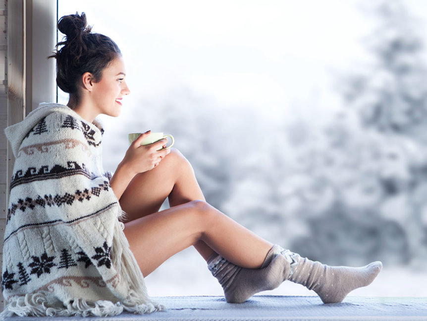 Woman enjoying her warm home after heating maintenance before winter